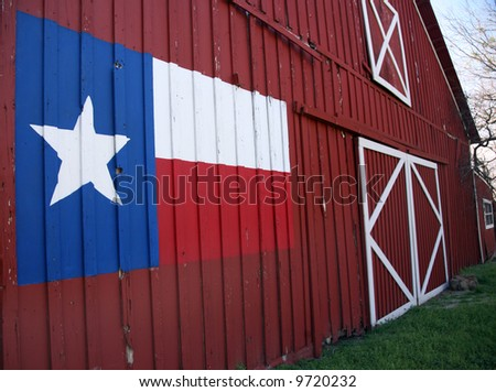 View of front of an old barn with State Flag of Texas painted on it. - stock photo
