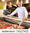 View of frozen meat with cheerful chef in the background - stock photo