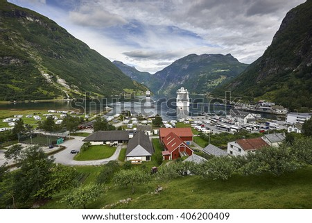 View of Geiranger Fiord, and a large passenger ship in the fjord - stock photo