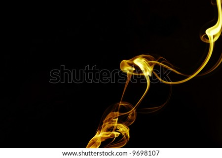 view of gold smooth smoke curling through the blackness - stock photo