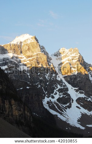 View of golden mountain peaks in the morning at moraine lake area, banff national park, alberta, canada - stock photo