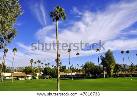 View of golf course with palms and clouds - stock photo