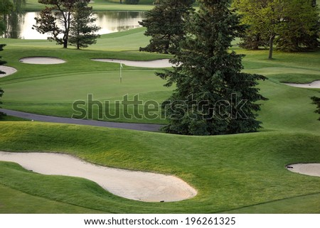 View of golf green with bunkers and water