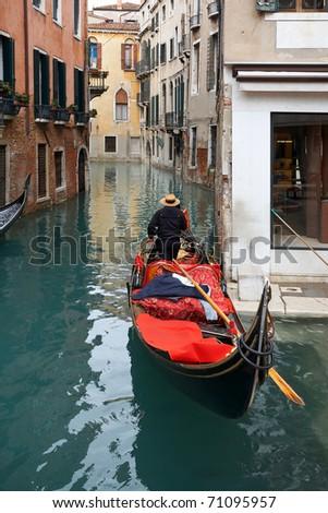 View of gondola with gondolier at narrow street of city. Venice - stock photo