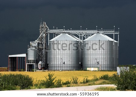 View of grain silos against stormy sky - stock photo
