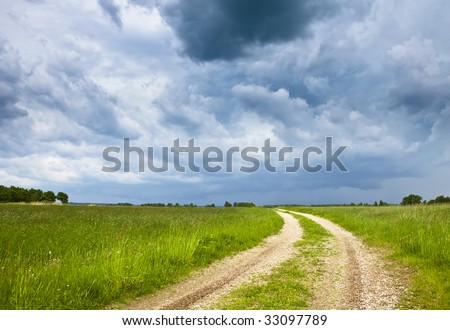 View of gravel road among green meadow and stormy sky. - stock photo