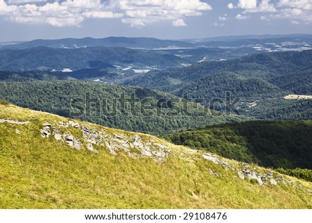 View of green mountain with meadow, blue mountains away and cloudy sky.
