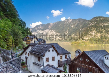 View of Hallstatt village with fancy mountain houses by Hallstatt lake among high Alp Mountains.