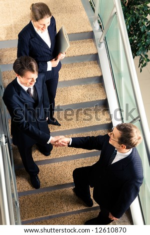 View of handshake of business partners met on the stairs in the office building - stock photo