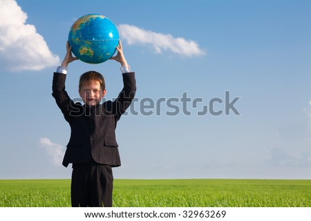 View of happy boy with globe standing in the field