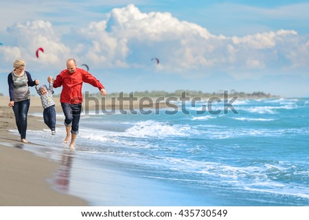 View of happy young family having fun on the beach.