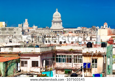 View of Havana including the dome of the Capitol against a clear blue sky and several decaying buildings - stock photo