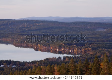 View of hills and ridges, lake this side. Vast ares of taiga forests in evening lit. - stock photo