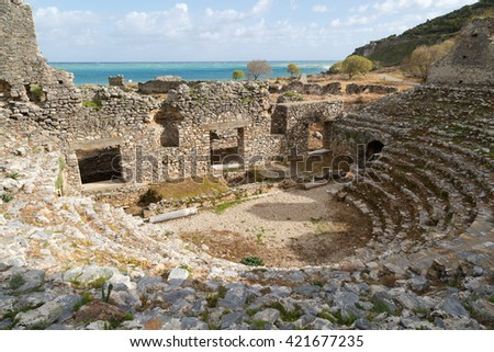 View of historical old amphitheater in Anemurium ancient city in Mersin, on cloudy blue sky background.