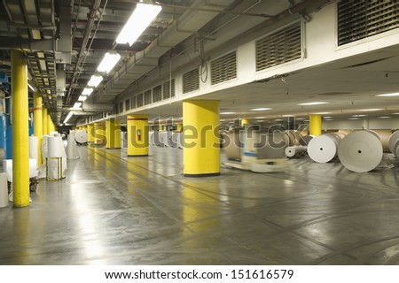 View of huge rolls of paper in spacious newspaper factory - stock photo