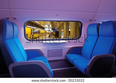 view of interior of a train,blue seats. through the window the underground station - stock photo