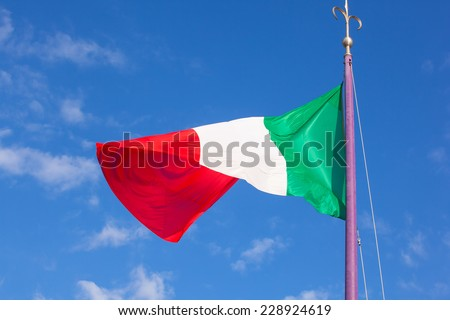 View of italian flag blowing in the wind - stock photo
