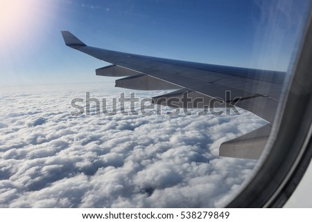 View of jet plane wing. Airplane in flight, view from plane window