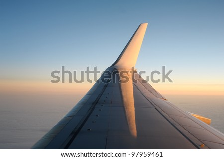 View of jet plane wing in clear evening sky. - stock photo