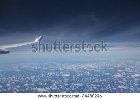 View of jet plane wing with cloud patterns