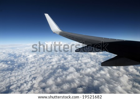 View of jet plane wing with cloud patterns and copy space
