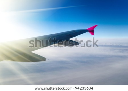 View of jet plane wing with sun - stock photo