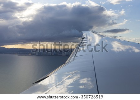 View of jet plane wing with the bay of Panama City with sunset light, Panama 2013. - stock photo