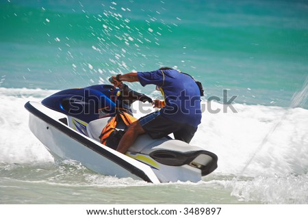 view of jetski rider fiercely struggling with ocean wave - stock photo
