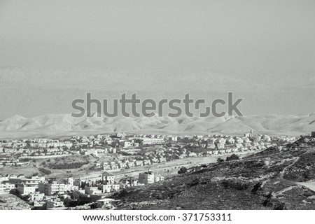 View of Judaean Desert and Maale Adumim town in haze from Mount Scopus in Jerusalem (Israel). Aged photo. Black and white. - stock photo
