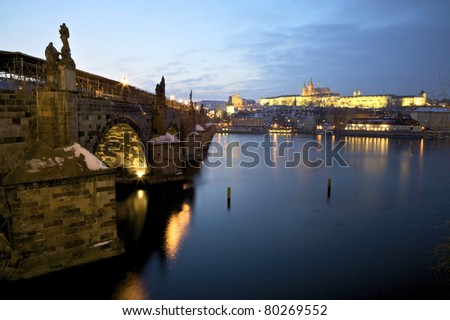 View of Karlu?v most (Charles Bridge) and Praz?sky? hrad (Prague Castle) from the bank of the River Vltava at dusk.
