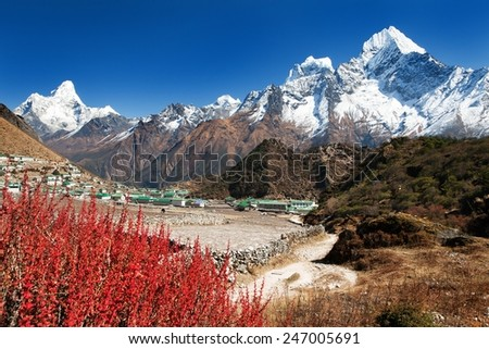 view of Khumjung village and beautiful himalayas near Namche bazar, Ama Dablam, kangtega and Thamserku - Way to Everest base camp - Nepal - stock photo