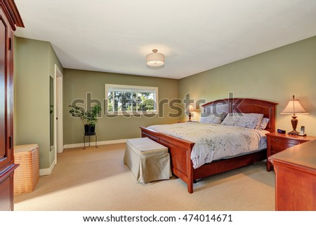 View of king size wooden bed with headboard in olive bedroom interior. Northwest, USA