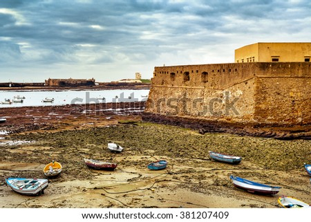 view of La Caleta Beach in Cadiz, with the Castle of Santa Catalina in the foreground ant the Castle of San Sebastian in the background - stock photo