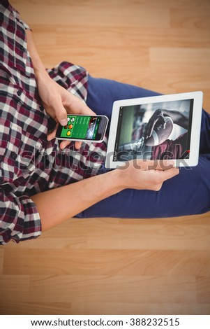 View of lecture app against hipster using smartphone while holding digital tablet - stock photo