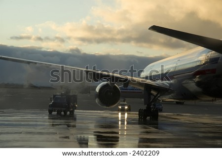 View of left side of commercial airplane being de-iced as it sits on a wet tarmac - stock photo