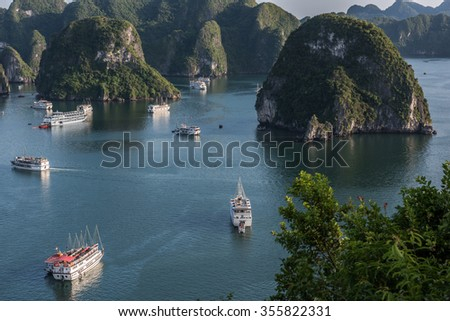 View of limestone karsts in Ha Long Bay, covered with green trees and ferns. Thousands of karst hills on the waters deliver an amazing view. Tourist boats are seen sailing on the water. - stock photo