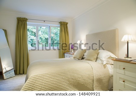 View of lit lamps by tidy bed in the bedroom - stock photo