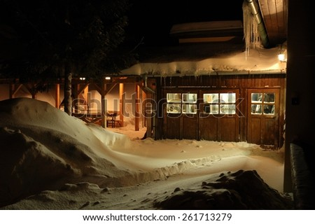 View of lit windows of house on winter evening with snow banks.
