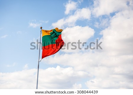 View of lithuanian flag waving on wind, on cloudy sky background.