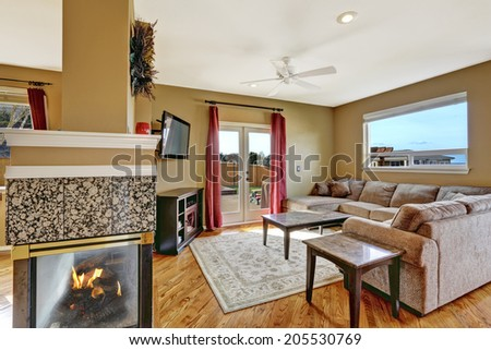 View of living room with beige sofa, wooden tables and tv. Room has walkout deck and fireplace