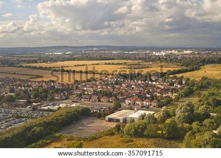View of London outskirts, England taken from the airplane in summer with trees, fields and clusters of houses - stock photo