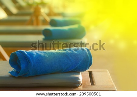 View of long chairs set by swimming-pool - stock photo