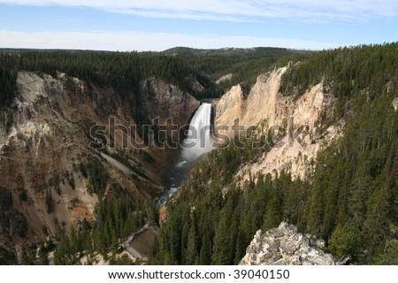 View of Lower Yellowstone Falls with Grand Canyon of the Yellowstone in Yellowstone National Park, with rough rock and trees on both sides. Blue sky with some clouds. - stock photo