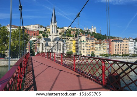 View of Lyon city from red footbridge on Saone river and church  - stock photo