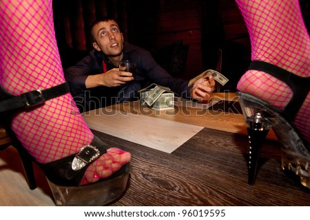 View of man offering money to a stripper on stage - stock photo
