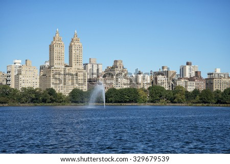 view of Manhattan from Central Park in front of the lake - stock photo