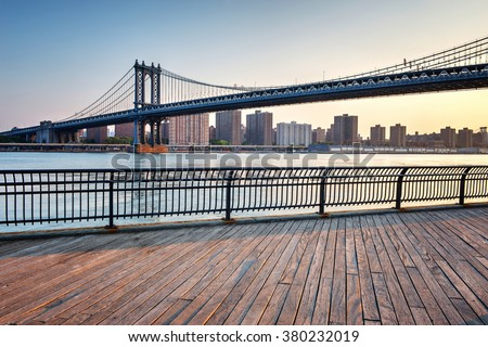 View of Manhattan Suspension Bridge Spanning the East River with View of Manhattan from Boardwalk in Waterfront Brooklyn Park, New York City, New York, USA - stock photo