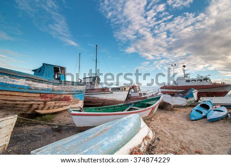 View of many traditional fishing boats anchored on low tide near Santa Luzia village, Portugal.