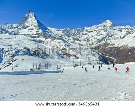 View of Matterhorn with some skiers skiing from Gornergrat, Zermatt, Switzerland - stock photo
