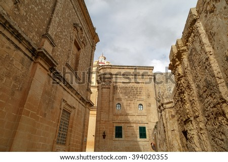 View of Mdina streets with limestone historical buildings around, on cloudy sky background.